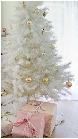 White christmas tree with gold decorations and pink gifts underneath